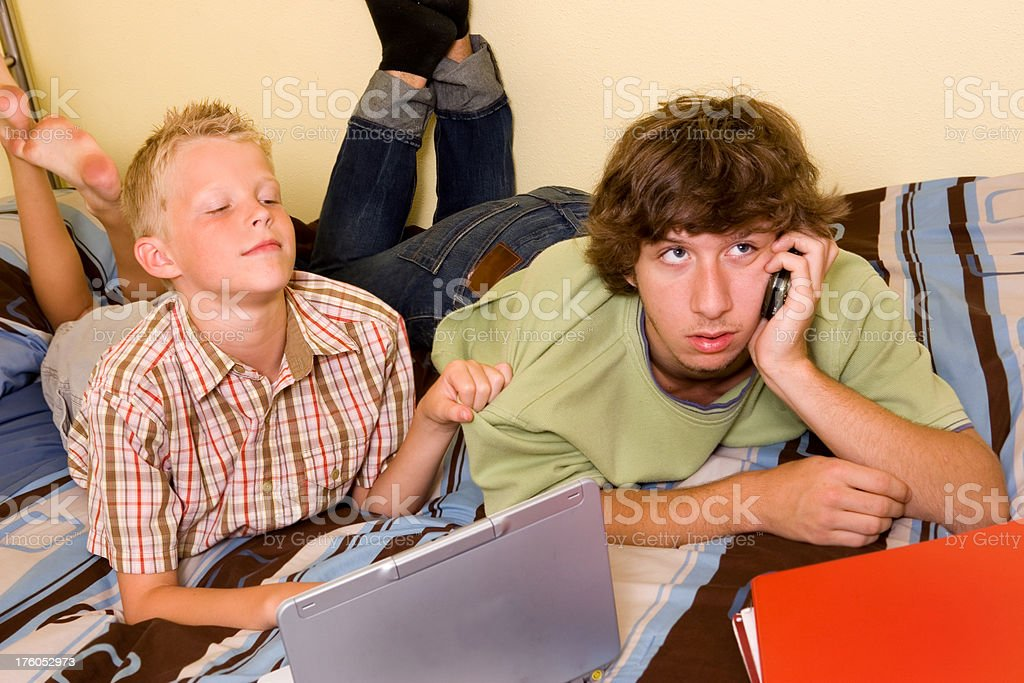 Boy trying to get his brother off the phone royalty-free stock photo