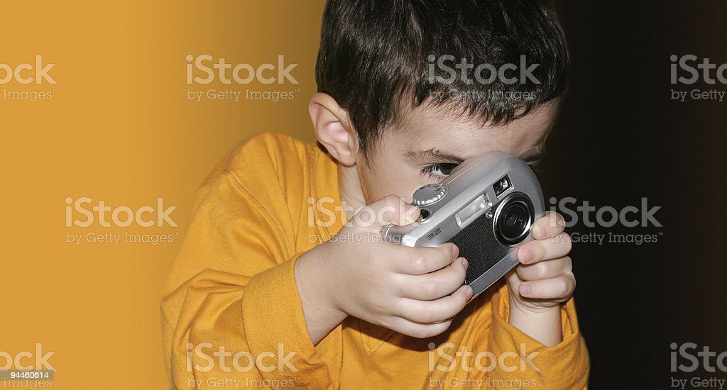 Boy trying to take a photograph stock photo