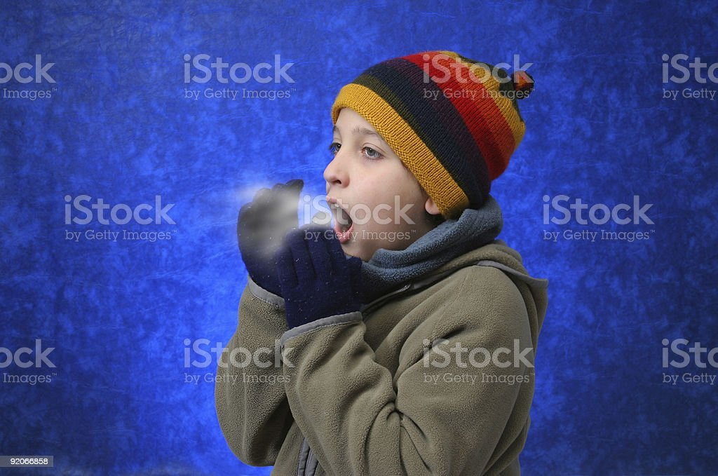 Boy trying to warm his hands stock photo