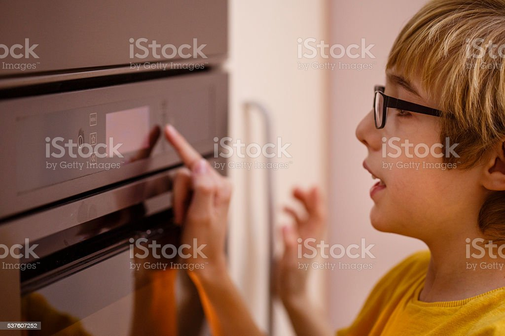 Boy turning oven on or off stock photo