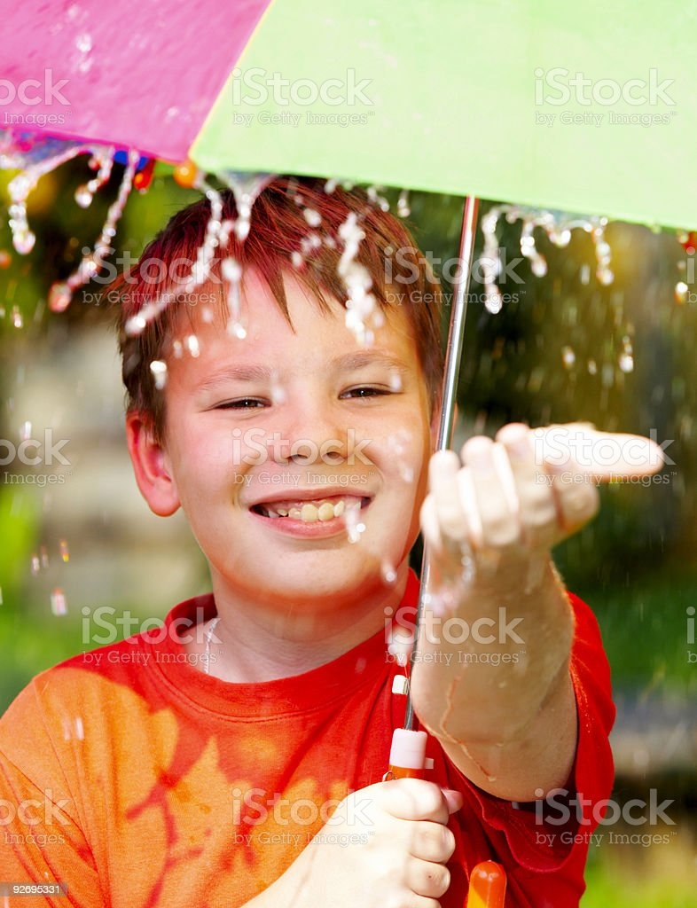 boy under an umbrella during a rain royalty-free stock photo