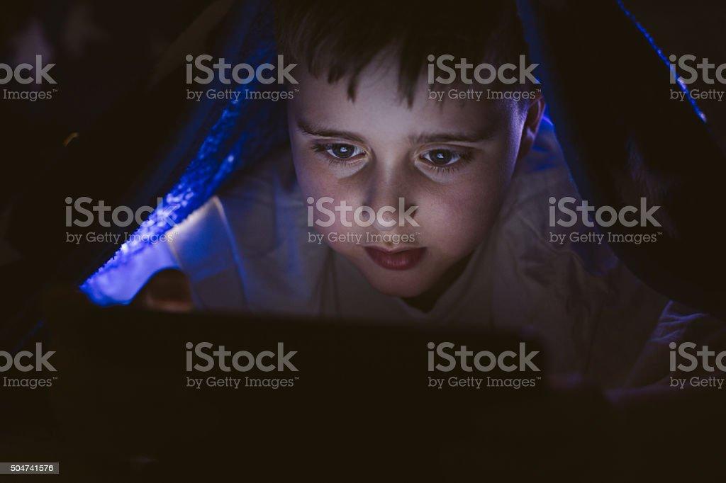 Boy under blaket using tablet stock photo