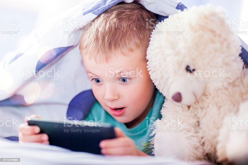 Boy under the covers, playing smartphone stock photo