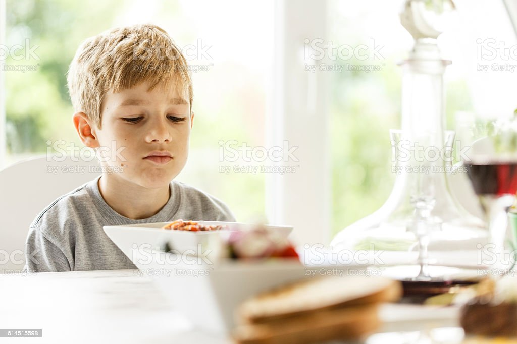Boy unhappy with his lunch stock photo