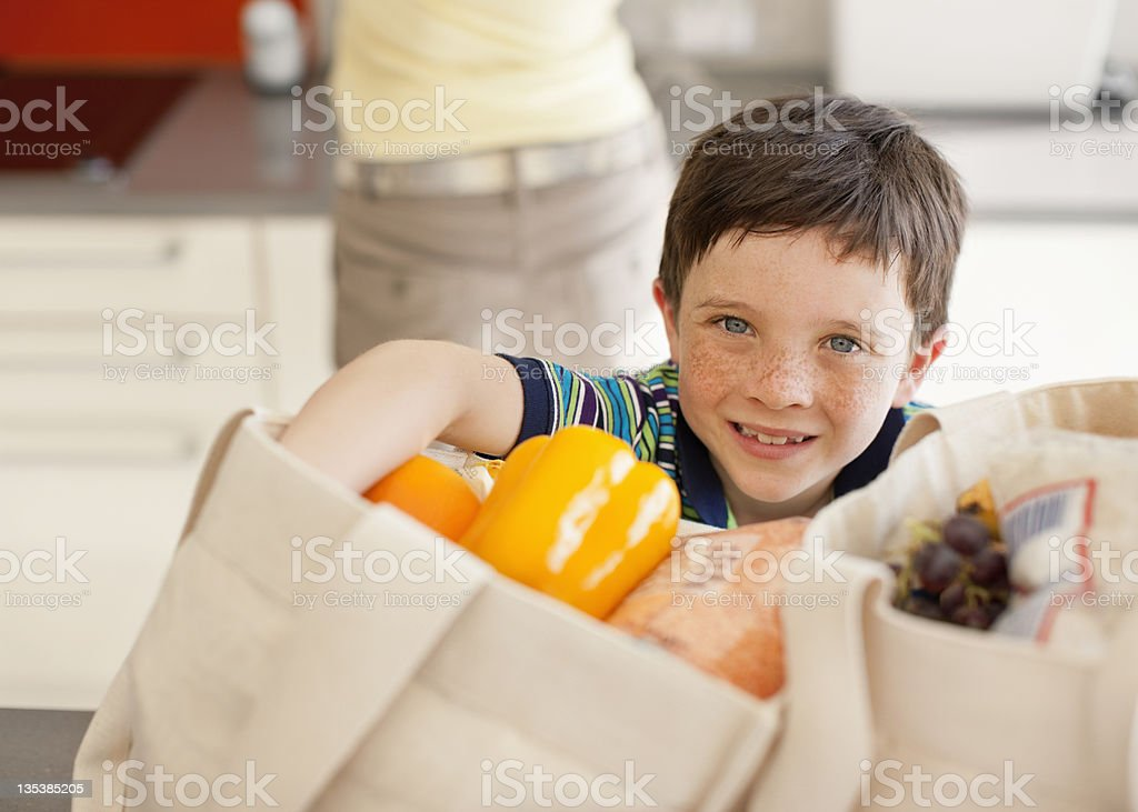 Boy unloading groceries from reusable bag stock photo