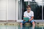 Boy using a digital tablet sitting near the pool
