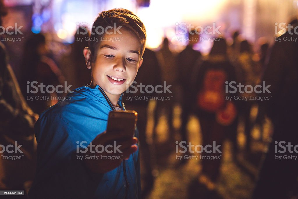 Boy using a mobile phone at night stock photo
