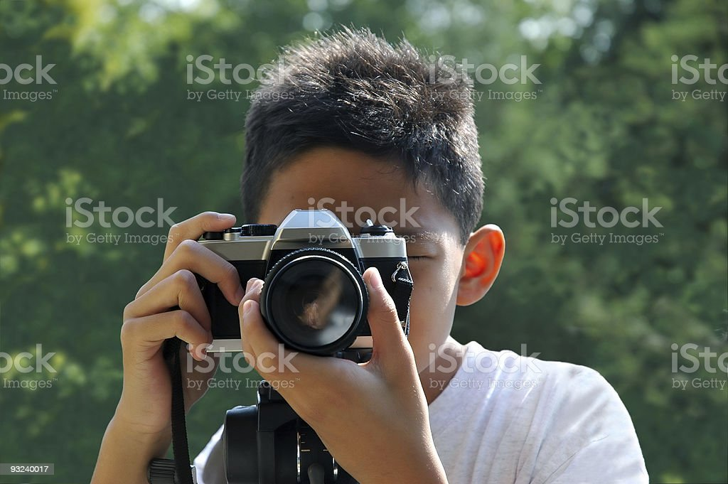 Boy using an old-fashioned film camera over blurred trees royalty-free stock photo