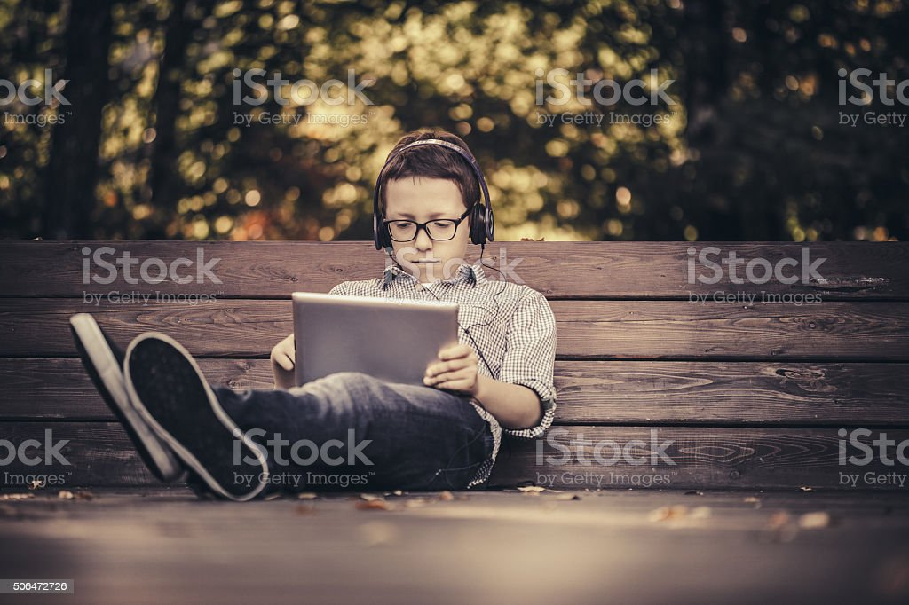 Boy using digital tablet sitting in the park stock photo