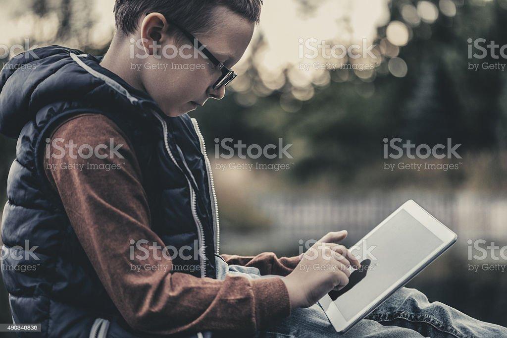 Boy using digital tablet sitting on wooden pier stock photo