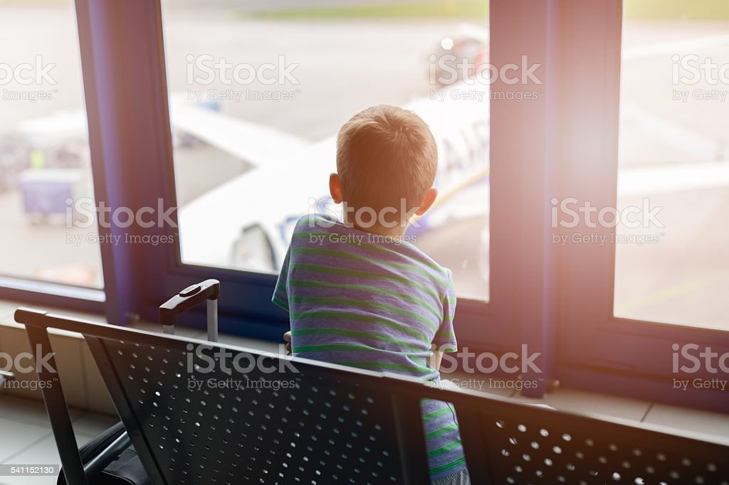 boy waiting for his plane at airport. stock photo