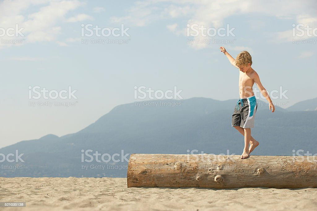Boy walking across a log on the beach stock photo