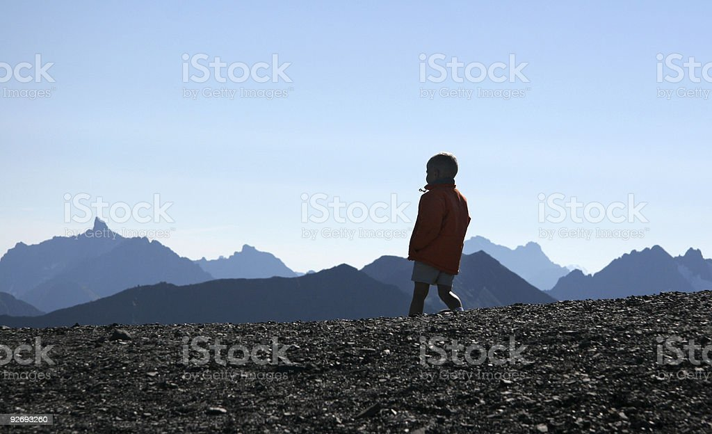 boy walking along mountain ridge royalty-free stock photo