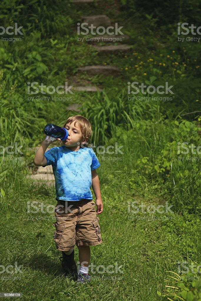 boy walking and drinking on the trail royalty-free stock photo