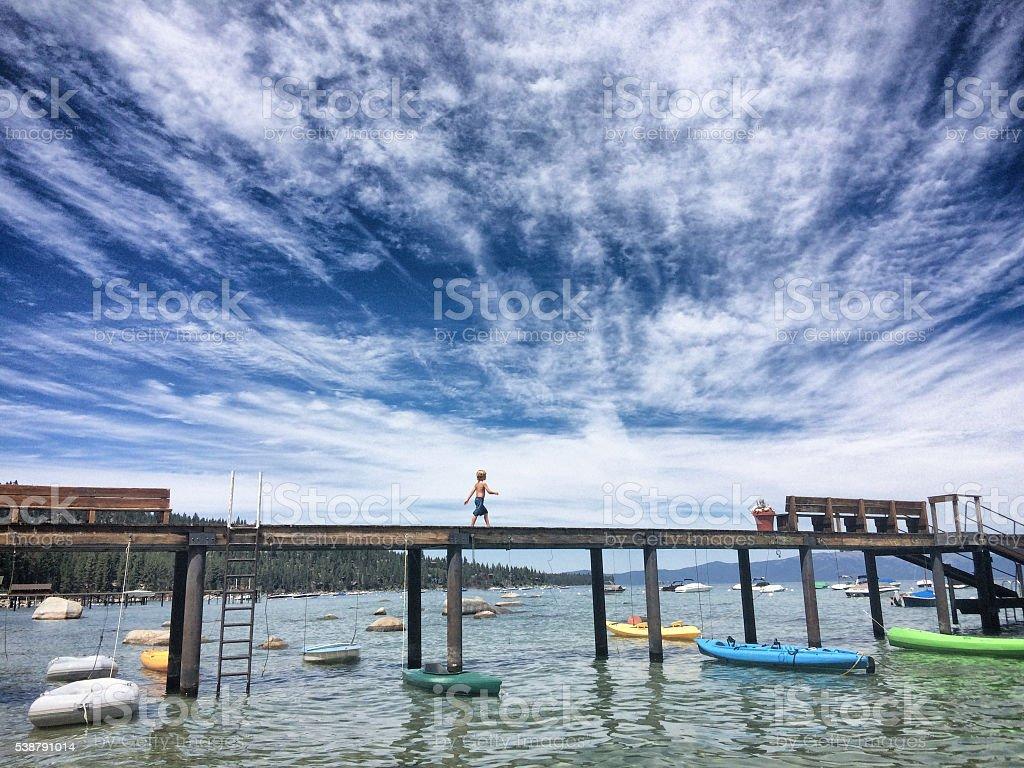 Boy walking on a dock on Lake Tahoe in summer stock photo