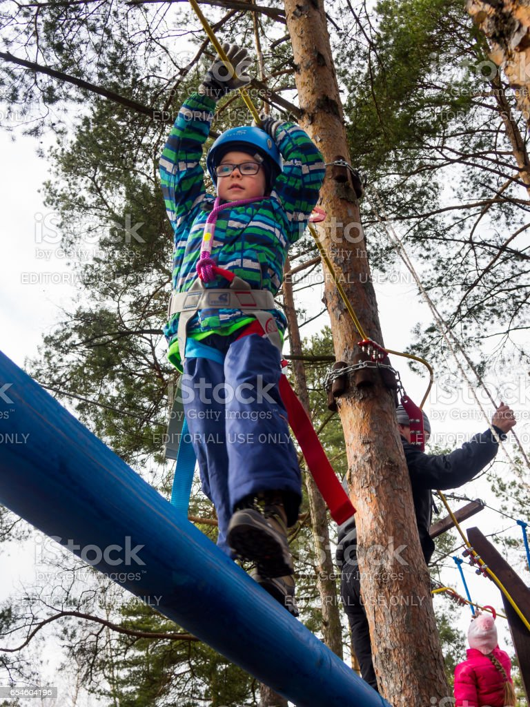 Boy walking on a log on a suspended classes in the tourist club stock photo