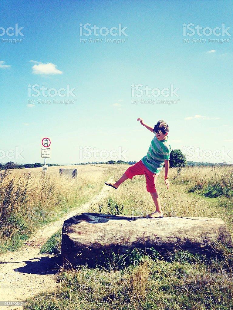 Boy walking on log stock photo