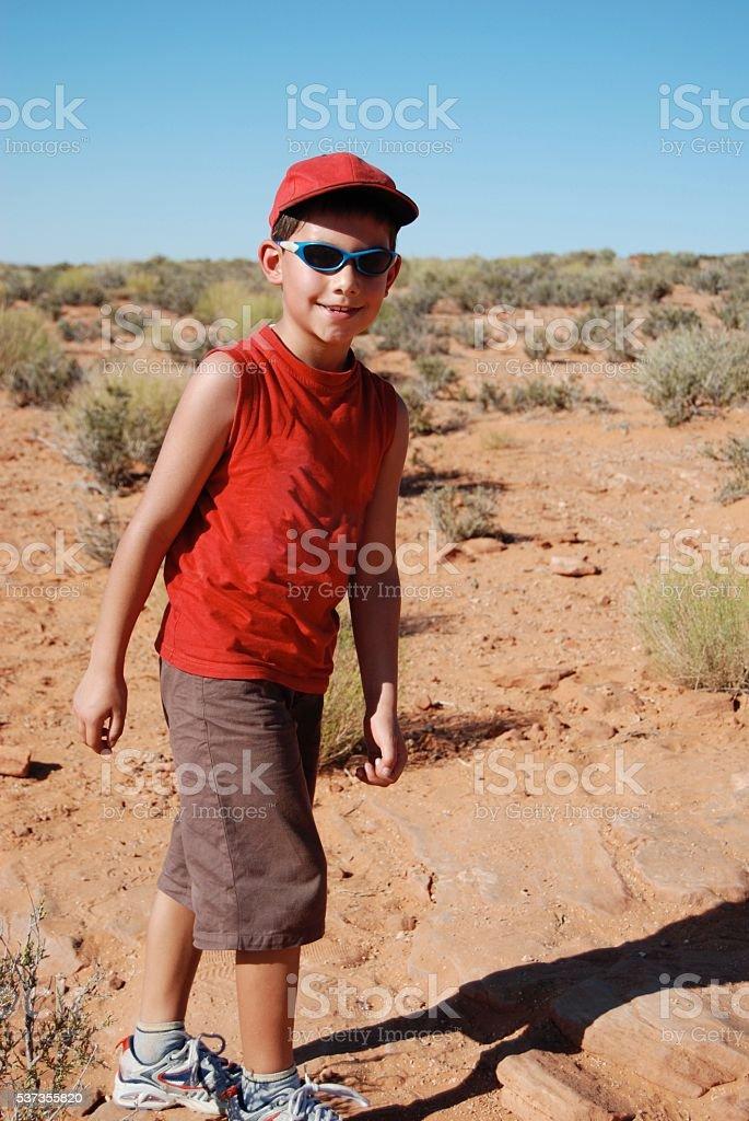 Boy walking through hot arid desert stock photo