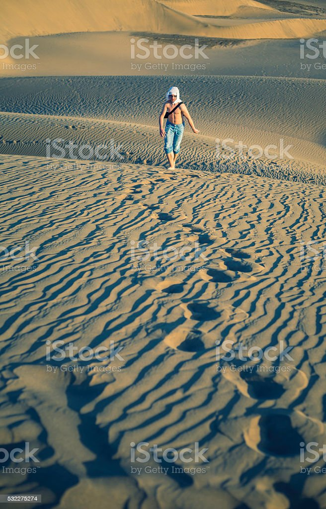 boy walking through sandy dunes stock photo