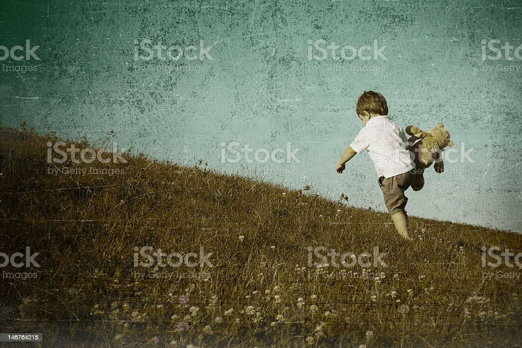 Boy Walking up hill with teddy stock photo