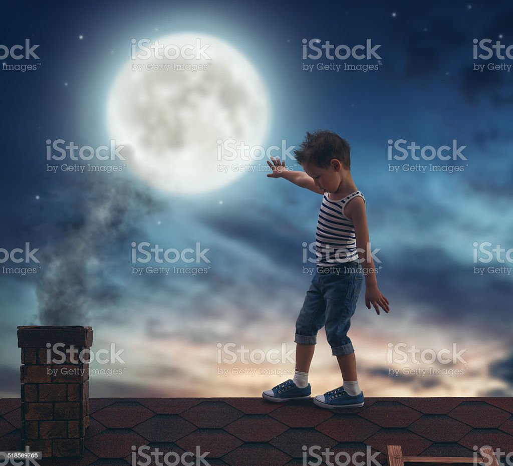 boy walks on the roof stock photo