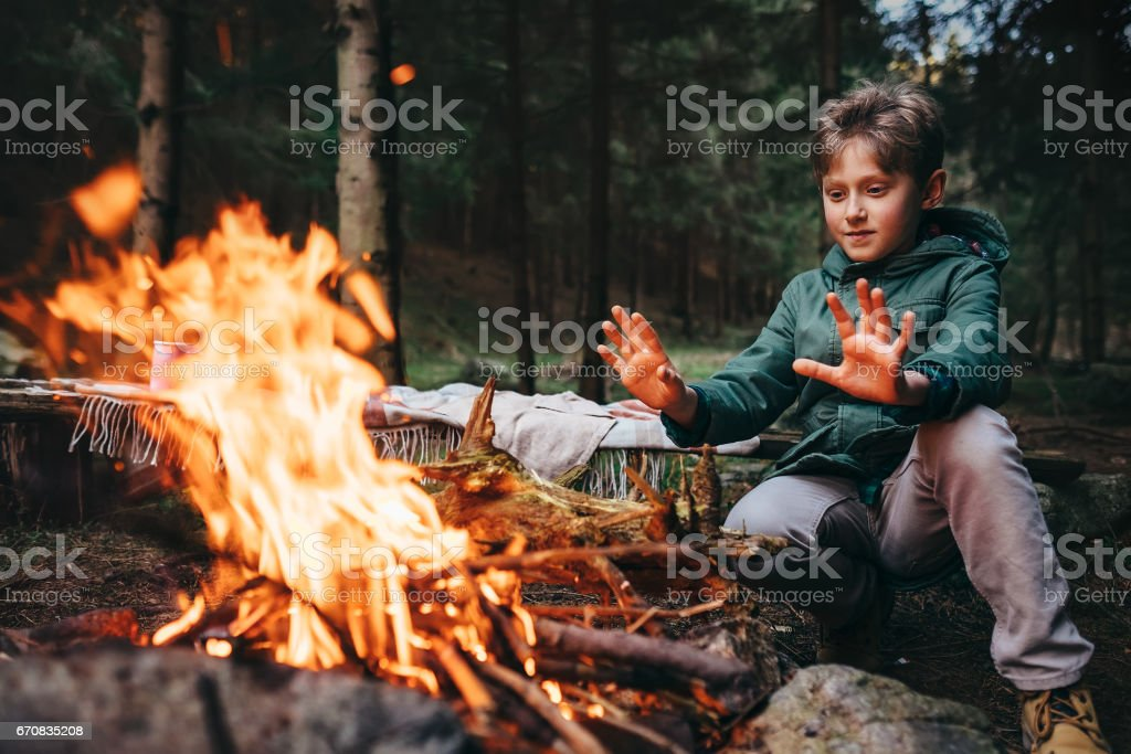 Boy warms his hands near campfire in forest stock photo