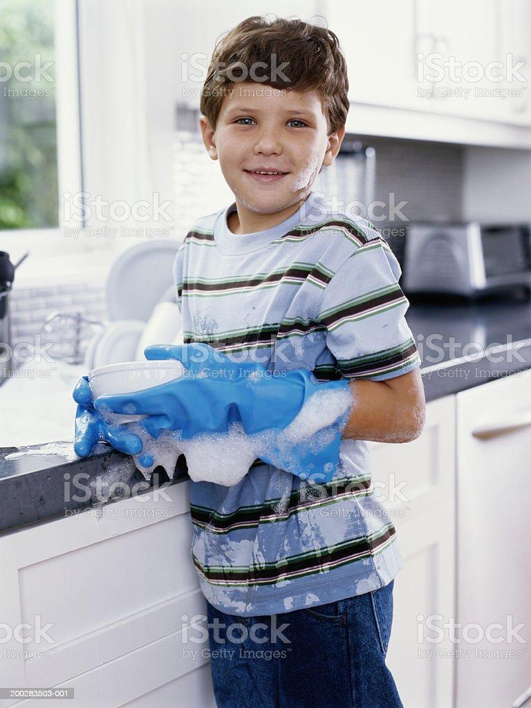 Boy (5-7) washing up at kitchen sink, smiling, portrait royalty-free stock photo