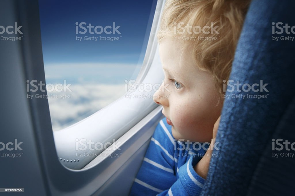 Boy watching sky through the airplane window stock photo