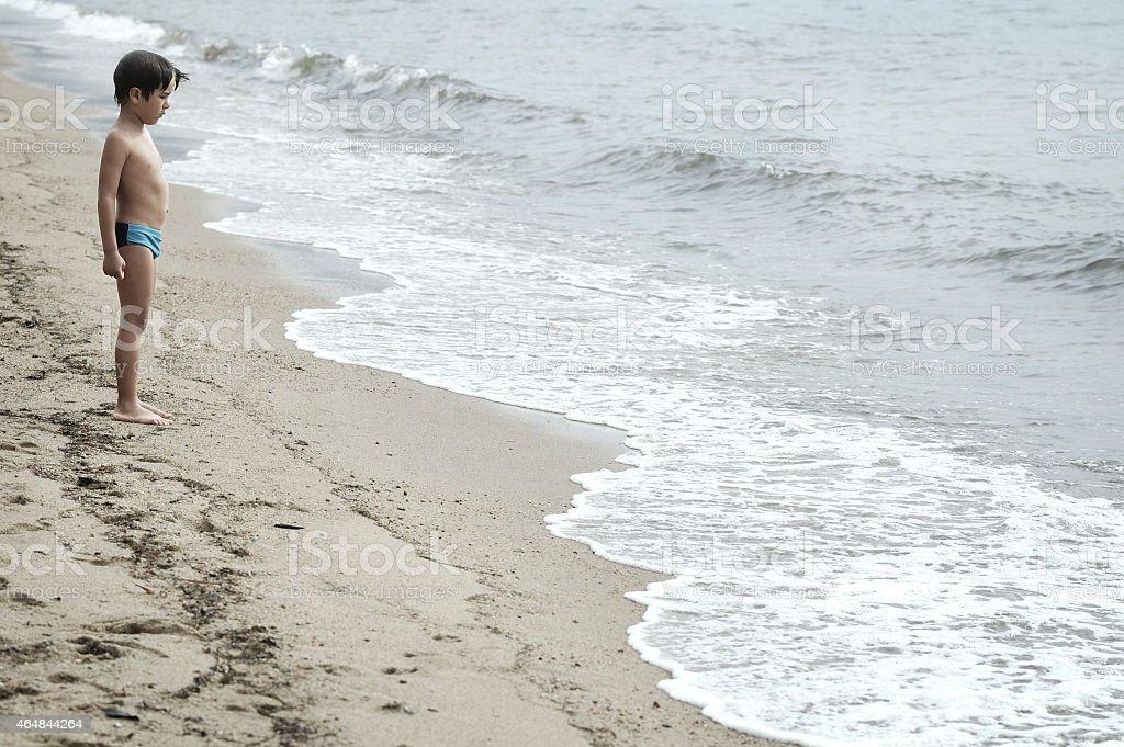 Boy watching the sea on the beach stock photo