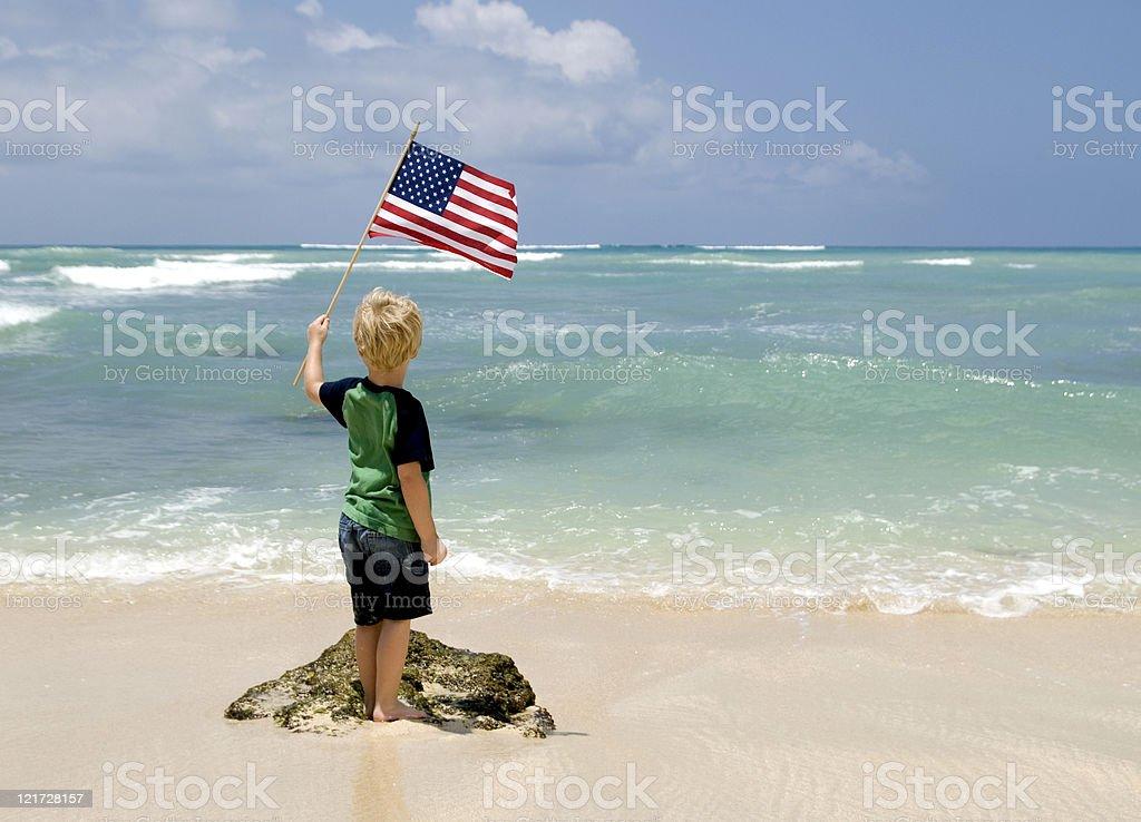 Boy Waving the American Flag on a Beach royalty-free stock photo