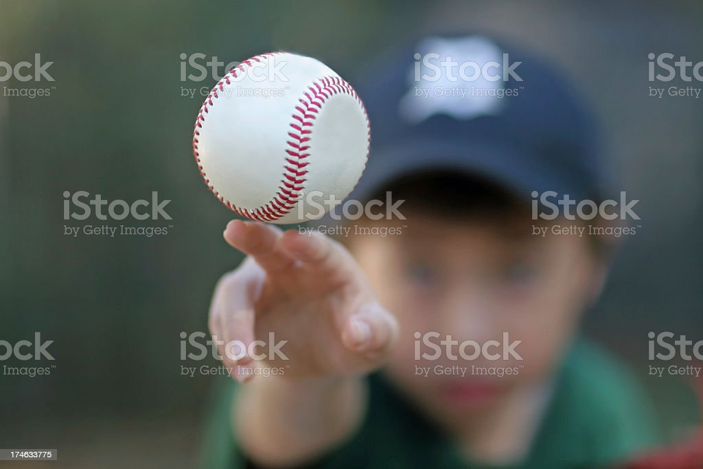 Boy wearing a hat throwing a baseball royalty-free stock photo