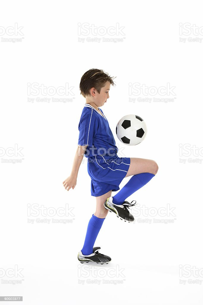 Boy wearing blue soccer kit and boots bouncing ball on leg stock photo