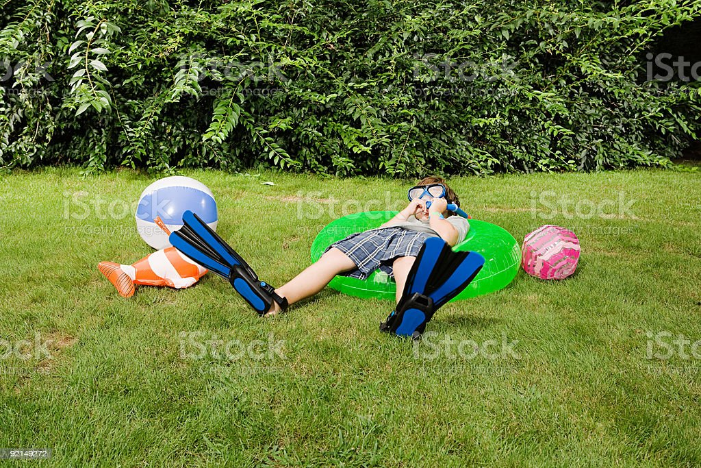 Boy wearing flippers and goggles on lawn royalty-free stock photo