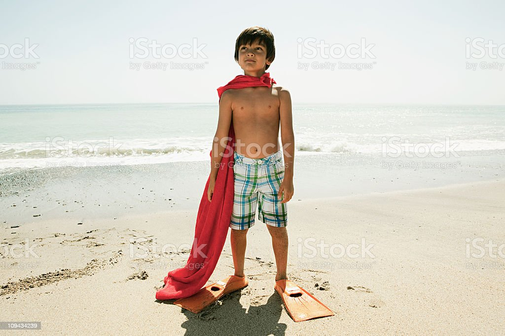 Boy wearing flippers and red cape on beach stock photo