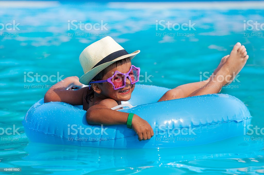 Boy wearing hat and glasses swimming in ring stock photo