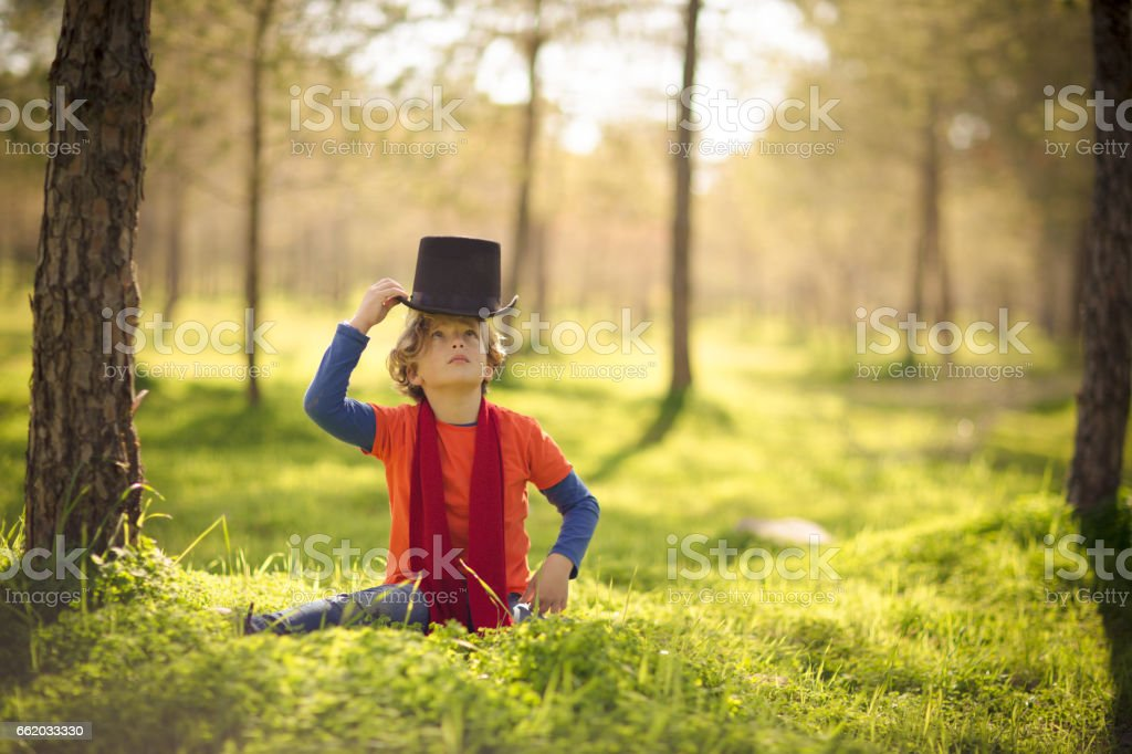 Boy wearing hat in a green park stock photo