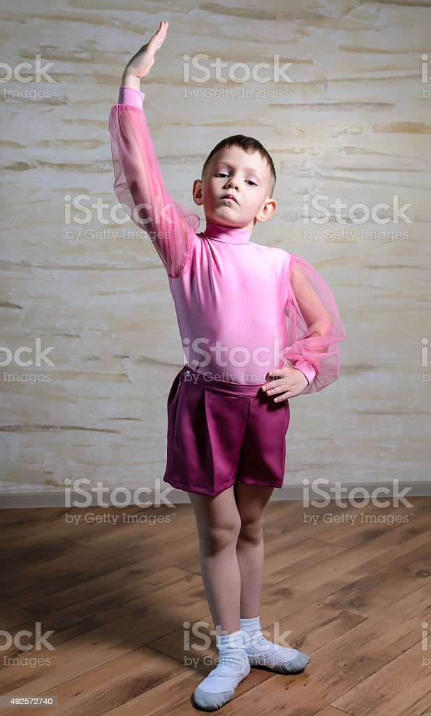 Boy Wearing Pink Dance Outfit Posing with Hand Up stock photo