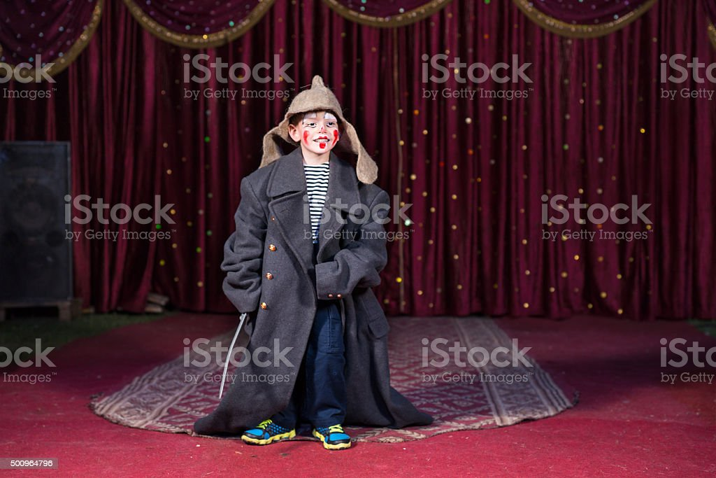 Boy wearing retro coat and Russian hat on stage stock photo