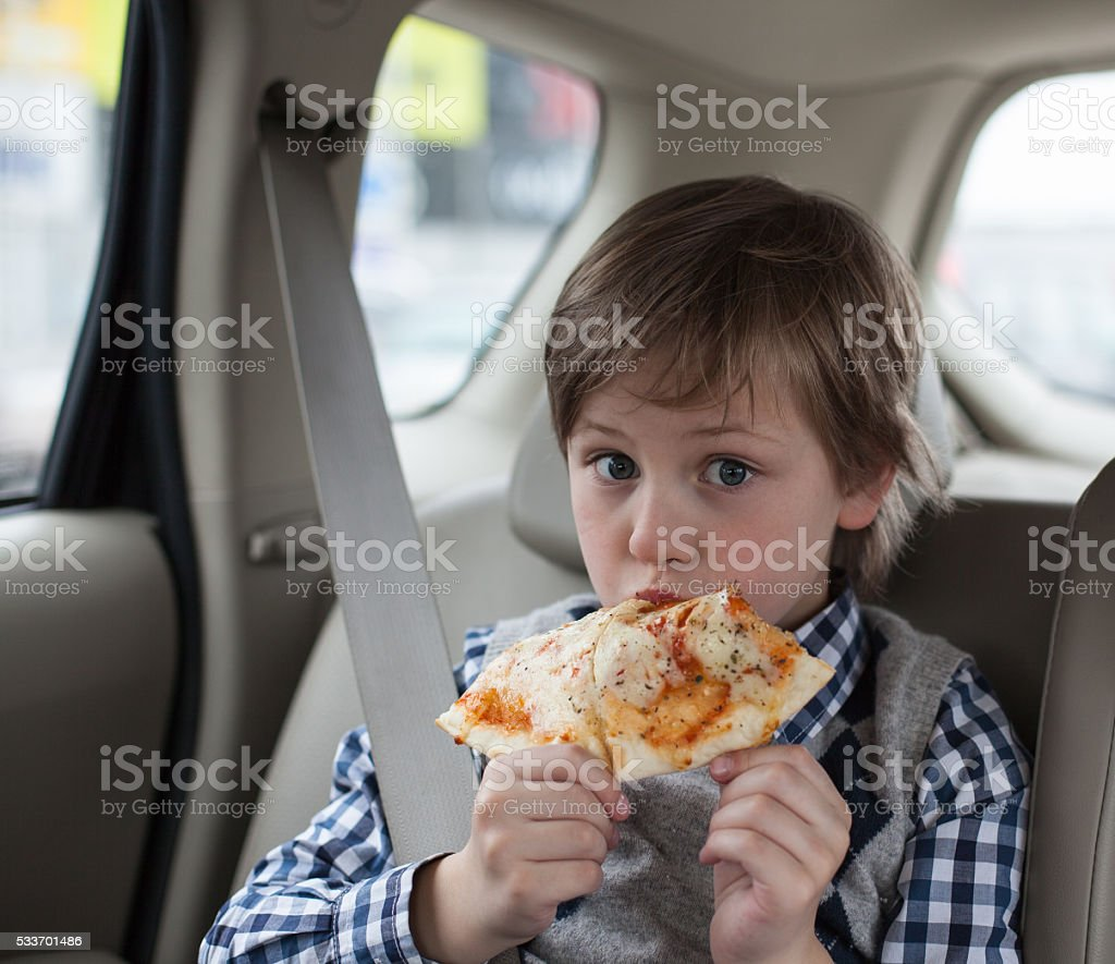 boy wearing safety  belt and eating pizza in the car stock photo