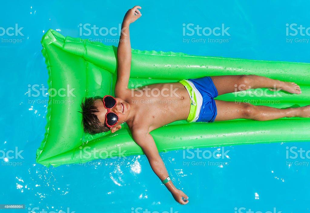 Boy wearing sunglasses relaxing on mattress stock photo
