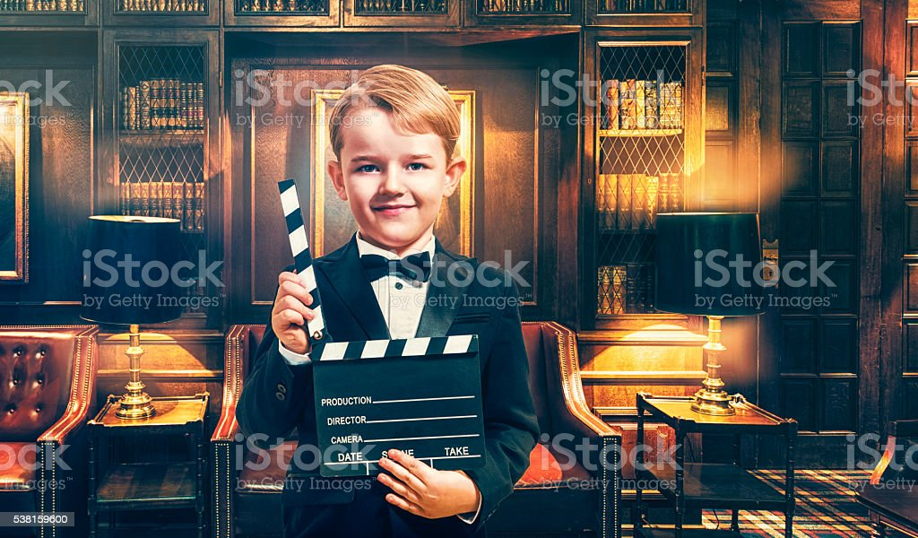 Boy wears tuxedo and holds film slate on location stock photo