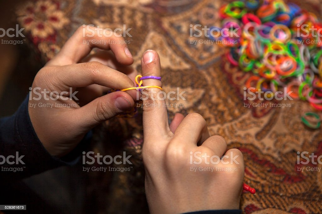 Boy weave decoration with rubber bands stock photo