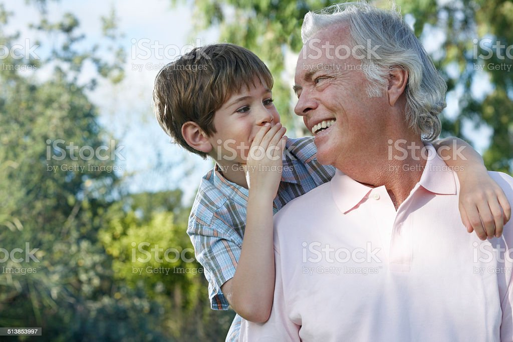Boy Whispering In Grandfather's Ear stock photo