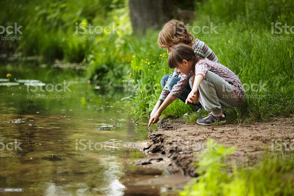 Boy with a girl near the water stock photo