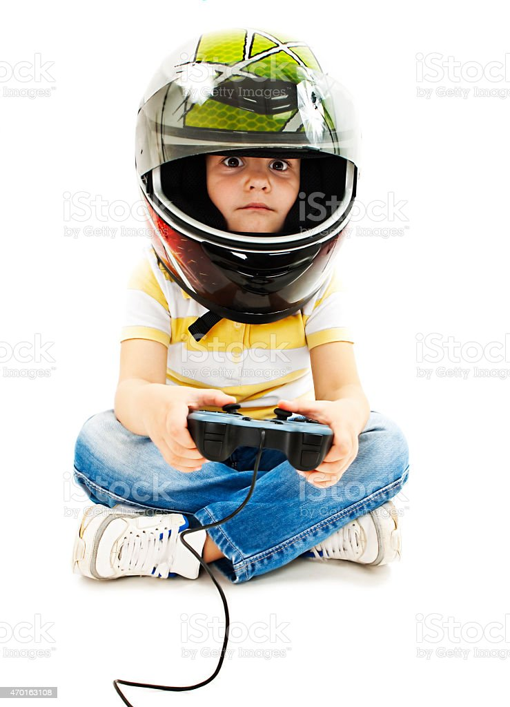 Boy with a helmet, using video game controller stock photo