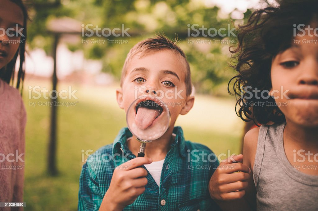 Boy with a magnifying glass making his tongue look big stock photo