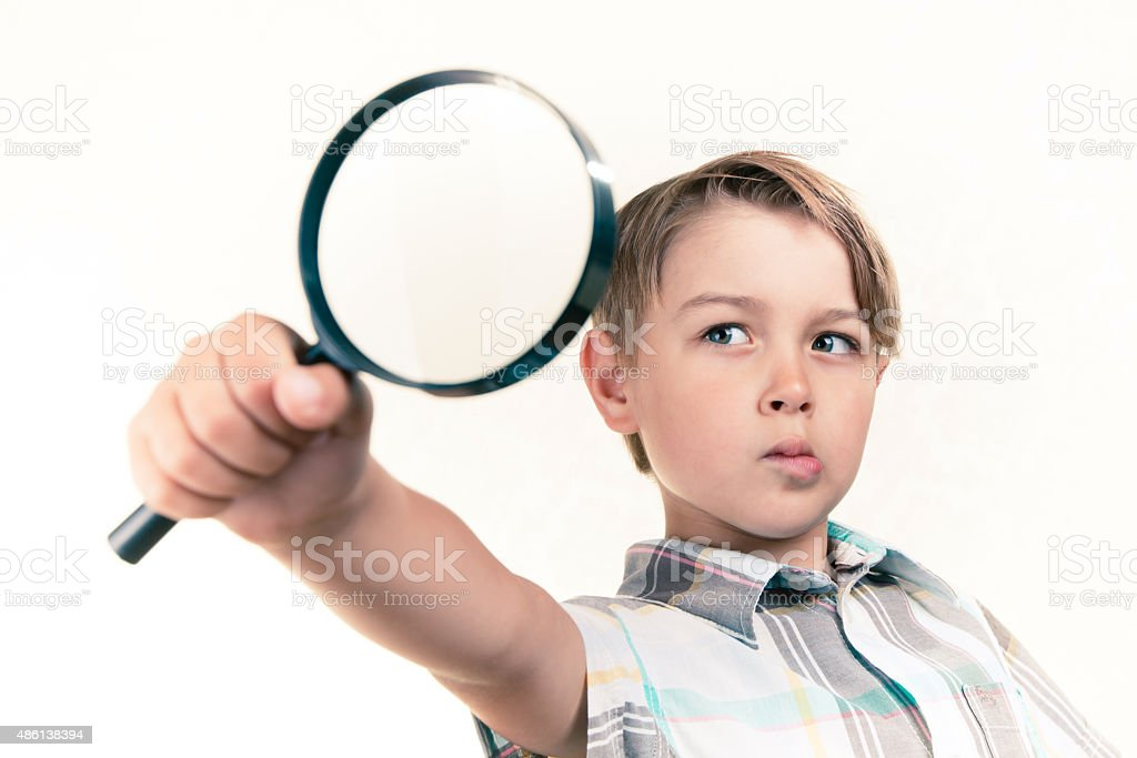 Boy with a magnifying glass stock photo