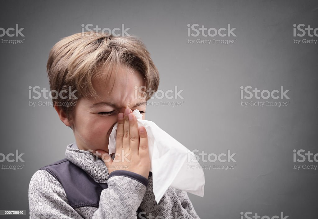 Boy with a tissue blowing his nose stock photo