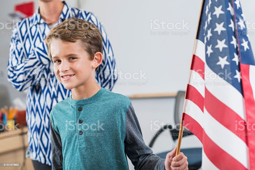 Boy with American flag in classroom stock photo