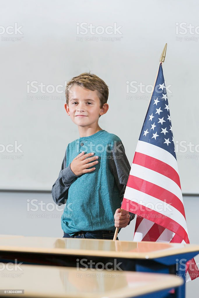 Boy with American flag saying pledge of allegiance stock photo